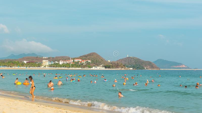 Hainan, China - May 14, 2019: On a bright sunny day on a tropical beach, people swim in the sea, relax on the sand.  stock image
