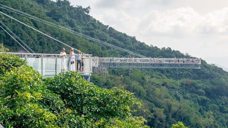 Hainan, China - May 17, 2019: Observation deck in the form of a glass bridge. Forest Park Yanoda. The mountains are covered with tropical jungles royalty free stock image