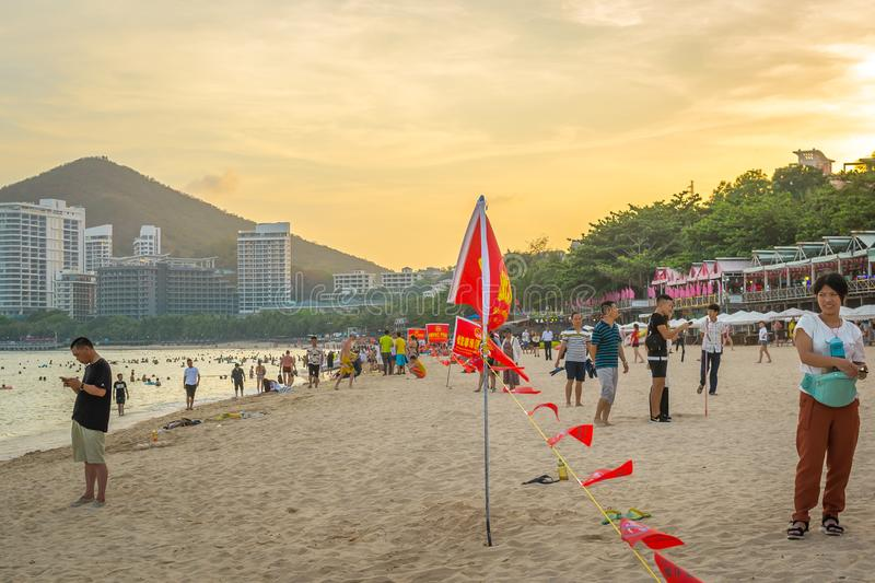 Hainan, China - May 14, 2019: Tropical beach, people swim in the sea, rest on the sand, golden twilight of sunset light.  stock photography