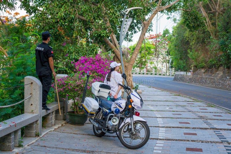 Hainan, Sanya, China - 16 de mayo de 2019: Los guardias del policía, de modo que los monos no aparezcan en el camino fotos de archivo