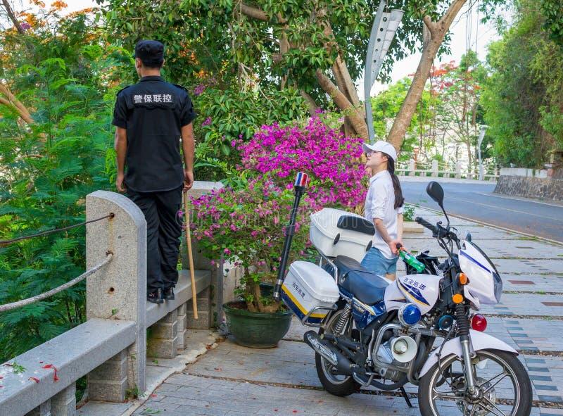 Hainan, Sanya, China - 16 de mayo de 2019: Los guardias del policía, de modo que los monos no aparezcan en el camino fotos de archivo libres de regalías