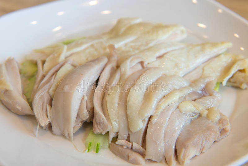 hainanese boiled chicken on white dish in restaurant stock photo