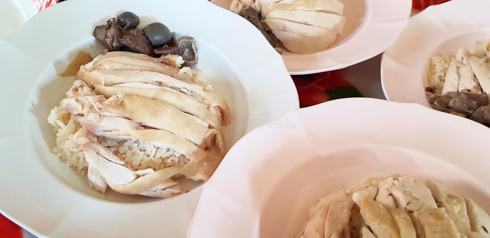 Hainanese chicken rice or steamed chicken with white rice on white plate for sale and serving customer royalty free stock image