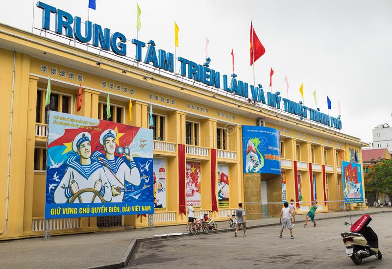 Haiphong, Vietnam - Apr 30, 2015: Exterior view of Haiphong Exhibition and Art Center with a lot of propaganda displaying in front stock photography