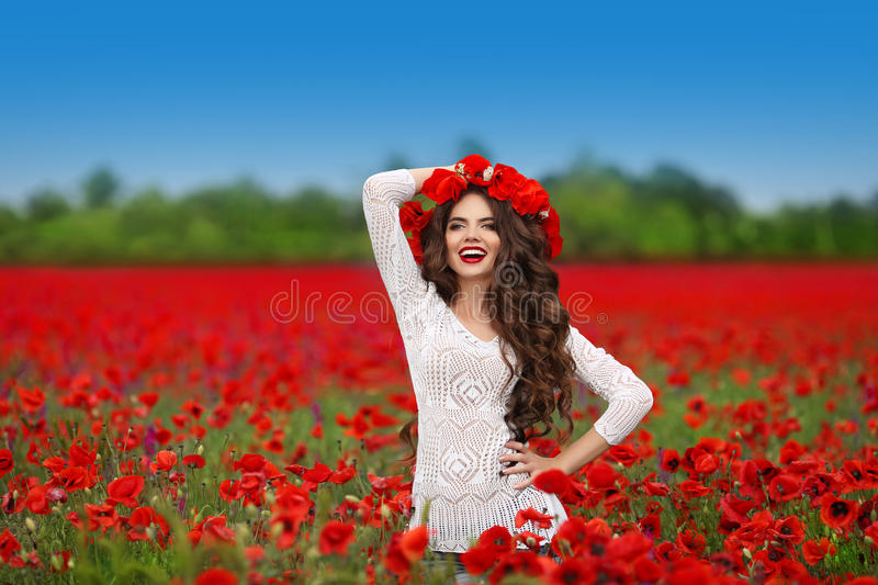 Hair. Beautiful happy smiling teen girl portrait with red flower. S on head enjoying in poppies field nature background. Carefree woman. Wellness well-being royalty free stock photography