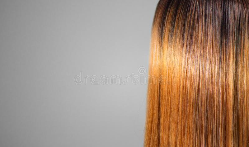 Hair. Beautiful healthy long smooth flowing brown hair close-up texture. Dyed straight shiny red hair background, coloring, extens. Ions, cure, treatment concept royalty free stock image