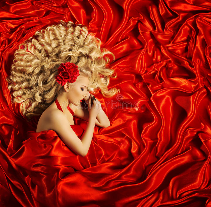 Hair Beauty Art, Woman Beautiful Curly Hairstyle, Fashion Model. Hair Beauty Art, Woman Beautiful Curly Hairstyle, Blonde Fashion Model Sleep on Red Silk Fabric royalty free stock photography