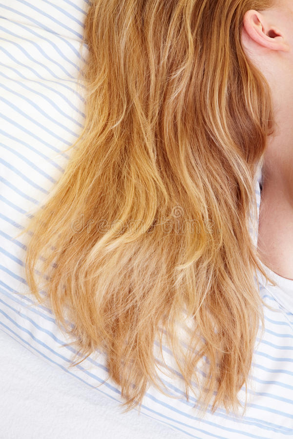 Hair in bed. Long blond hairs on the sheets in a bed royalty free stock photo