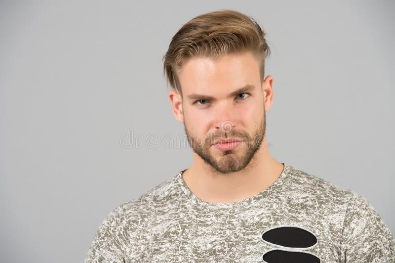 Hair care in barbershop or beauty salon. Macho with beard on unshaven face. Bearded man with blond hair and haircut. Handsome guy stock images