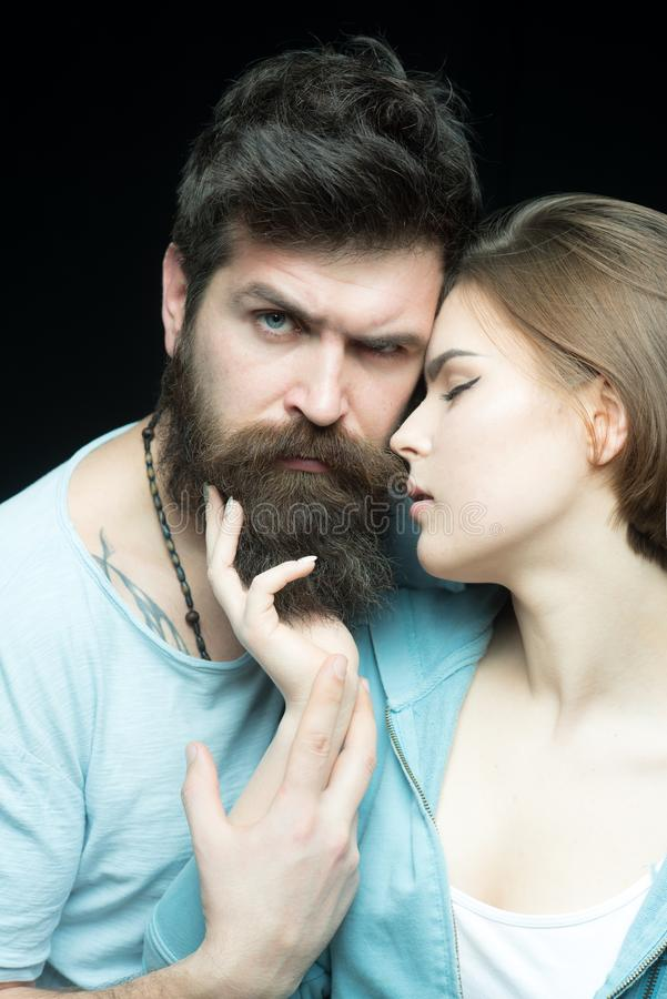 Hair care and barbershop concept. She likes his soft beard. Women love bearded brutal and masculine guys. Hipster. Bearded cuddling sensual girl. Make hair soft royalty free stock photography