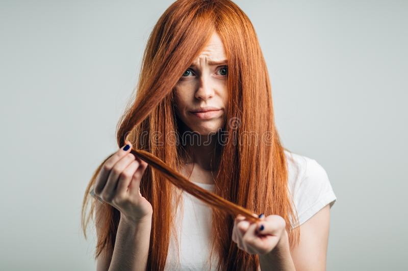 Sad redhead girl holding her damaged hair looking at camera. stock image