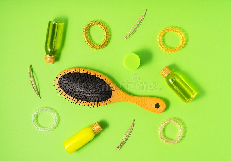 Flat lay of hair care products and styling items on green background. Women beauty and beauty salon cosmetics concept. Hair care products and styling items on royalty free stock image