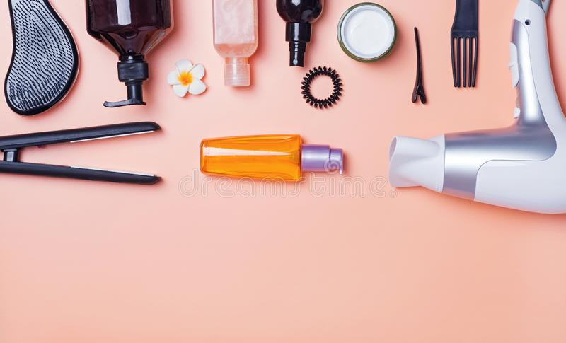 Hair care produts and styling items on orange background. Top view. Beauty salon concept royalty free stock image