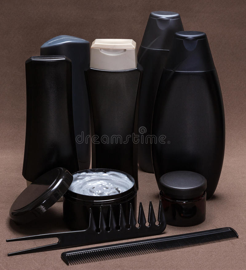 Hair care and styling products and accessories. Black and gray cosmetic containers, extra wide tooth and fine-tooth combs on brown textured surface royalty free stock photo