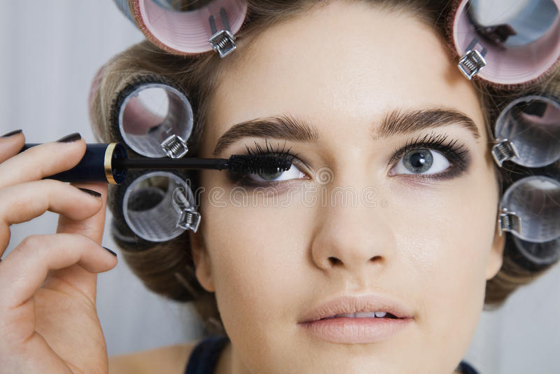 In Hair Curlers modèle appliquant le mascara photos stock