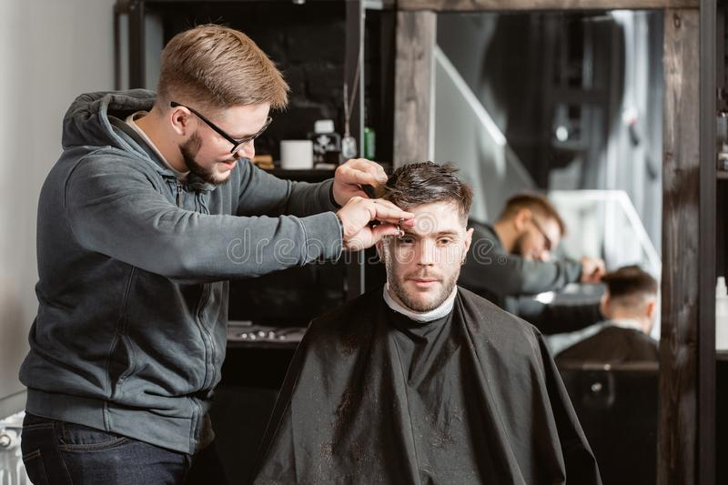 Hair cutting with metal scissors. Master cuts hair and beard of men in the barbershop, hairdresser makes hairstyle for a. Young man royalty free stock images