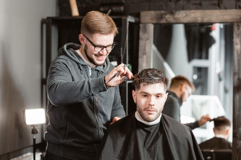 Hair cutting with metal scissors. Master cuts hair and beard of men in the barbershop, hairdresser makes hairstyle for a. Young man stock photography
