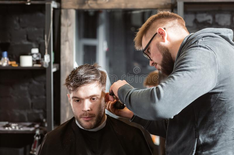 Hair cutting with metal scissors. Master cuts hair and beard of men in the barbershop, hairdresser makes hairstyle for a stock photos