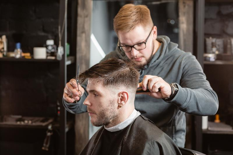 Hair cutting with metal scissors. Master cuts hair and beard of men in the barbershop, hairdresser makes hairstyle for a royalty free stock photo