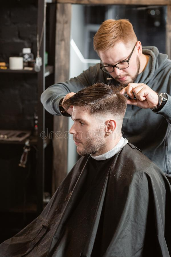 Hair cutting with metal scissors. Master cuts hair and beard of men in the barbershop, hairdresser makes hairstyle for a stock photography