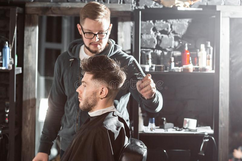 Hair cutting with metal scissors. Master cuts hair and beard of men in the barbershop, hairdresser makes hairstyle for a stock image