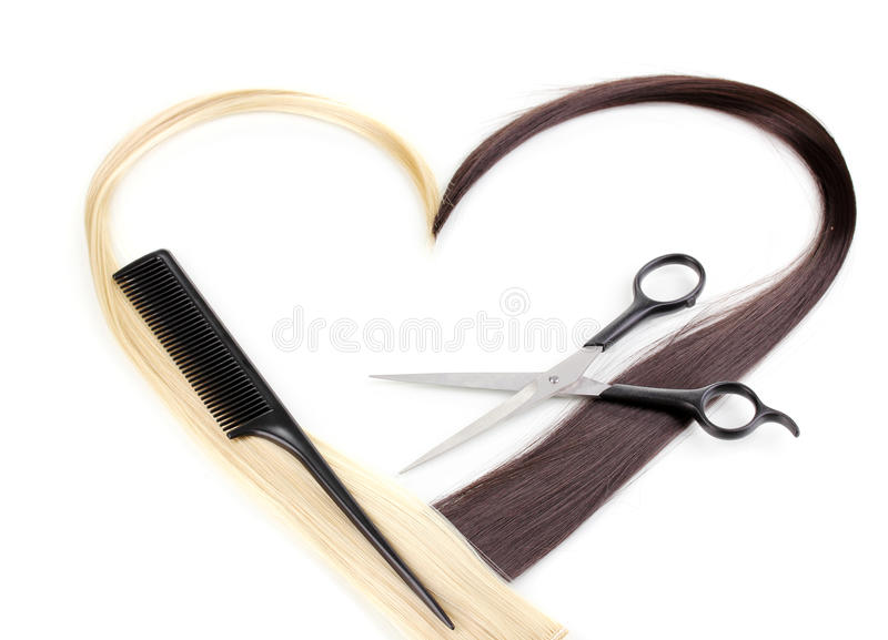 Hair cutting shears and comb. Shiny blond and brown hair with hair cutting shears and comb over the white stock photo