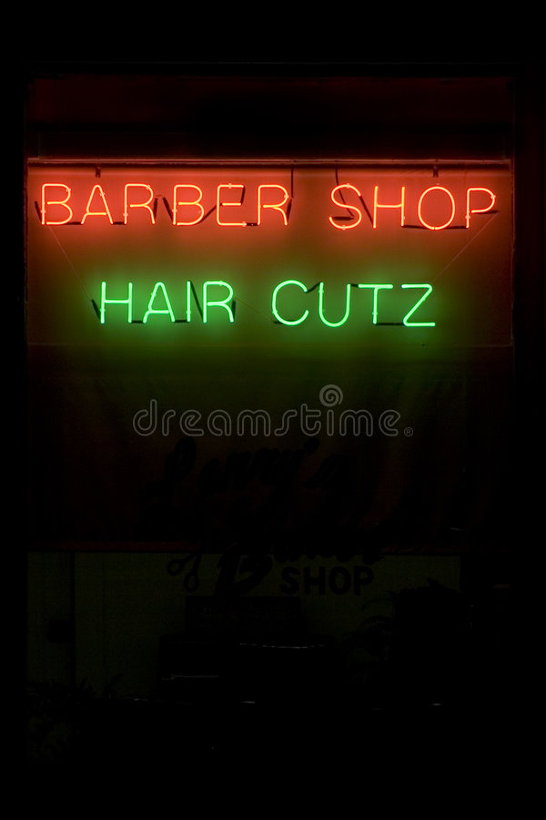 Hair Cutz. A lighted neon barbershop sign isolated on solid black background royalty free stock photo