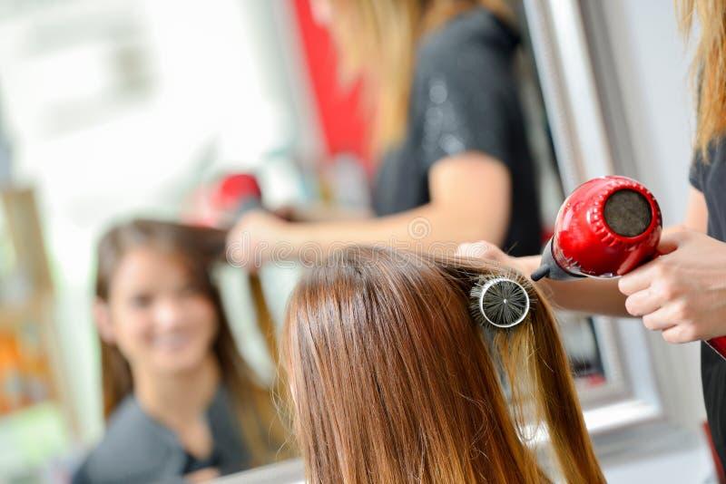 Hair dresser drying customer`s hair stock photography