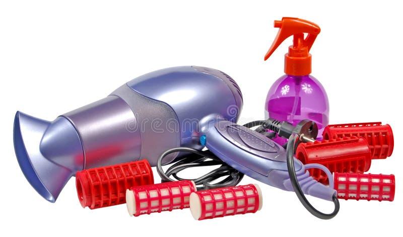 Hair dryer, hair curlers and plastic bottle a spra stock photos