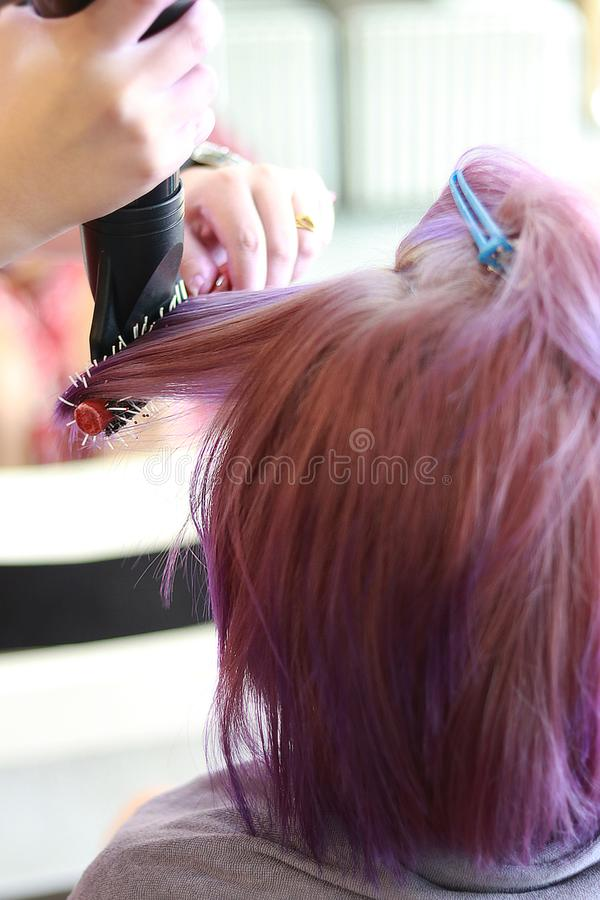 Hair dryer on purple. The hairdresser use a roll hairbrush and hair dryer blow on the purple hair in salon royalty free stock images