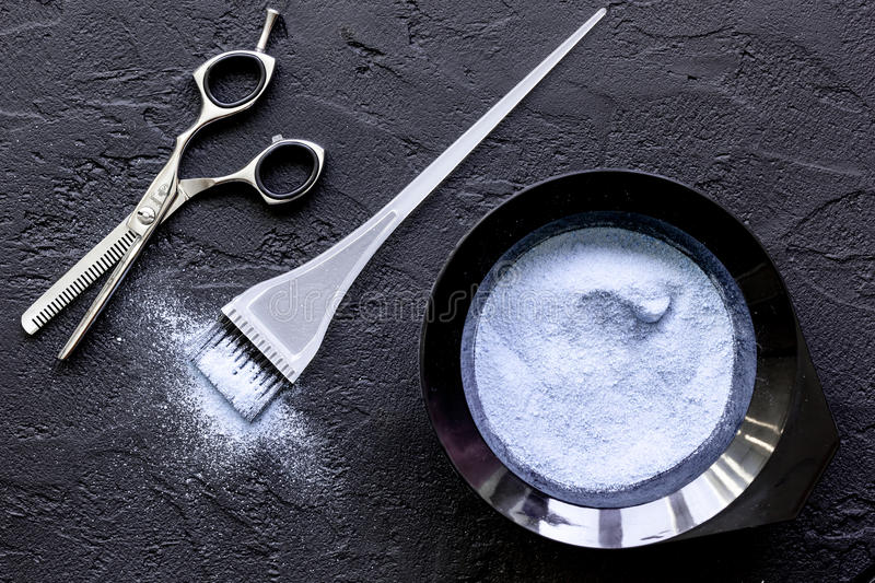 Hair dye with brush on dark background top view stock photo