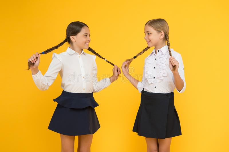 Hair easy to do yourself. Adorable little girls with plaited hair on yellow background. Cute small children holding long. Hair braids. Braiding and styling hair stock photo