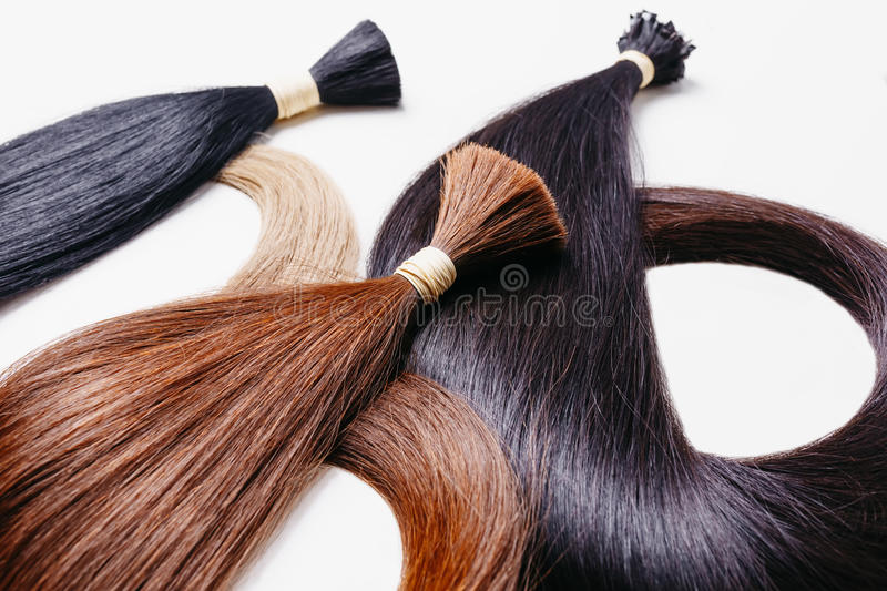 Hair extensions of three colors on a white background. copyspace selective focus stock photography