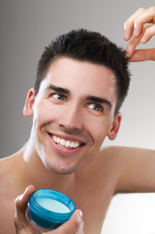 Hair gel. Young handsome man applying hair gel close up royalty free stock images