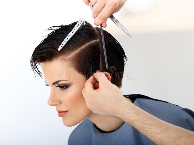 Hair. Hairdresser Cutting Womans Hair in Beauty Salon. royalty free stock photography