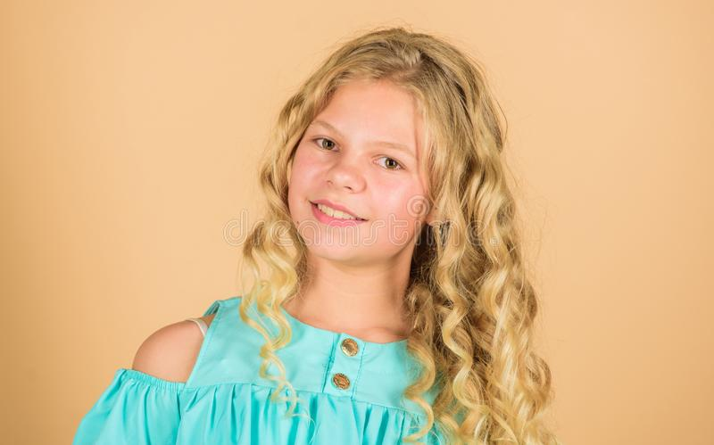 Hair health and care. hairdresser salon. beauty and fashion. long blond curly hair. beautiful little girl fashion model. Happy little girl with long healthy stock image