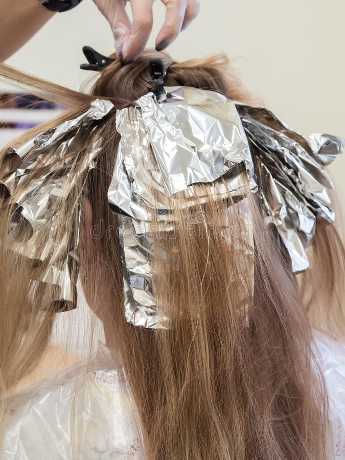 Hair highlights in the beauty salon. The foil on the hair while highlighting stock photo