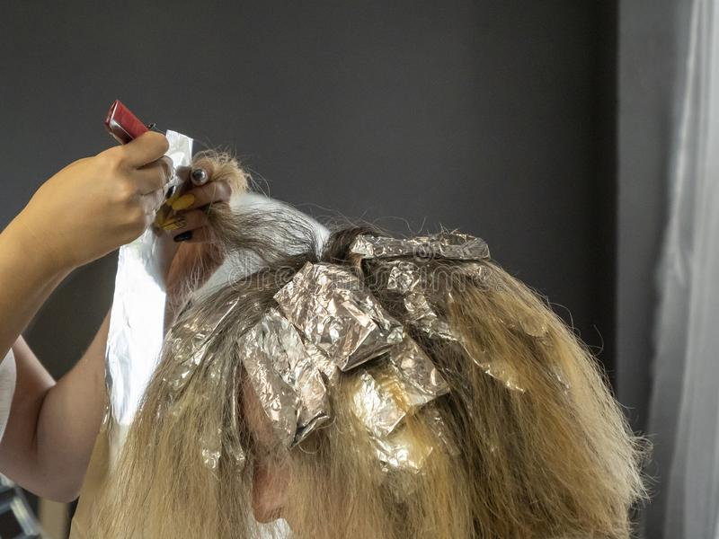 Hair highlights. Hairdressing. Comb and foil in the hands of a hairdresser. Wrapping strands in foil. Bleaching hair. Beauty saloon royalty free stock photos