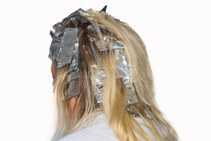 Hair highlights wrapped in aluminum foil. Woman with blond hair in preparation for hair dyeing. Hair highlights wrapped in aluminum foil stock image