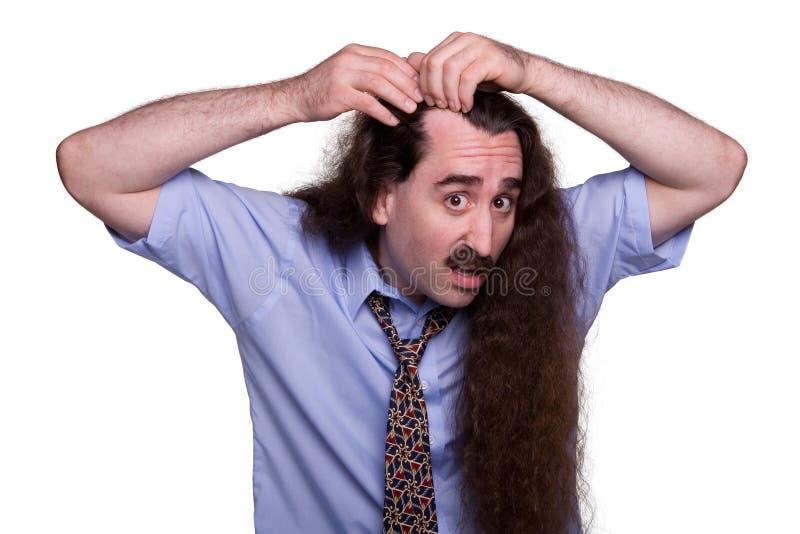 Hair Loss. A balding man inspecting his receding hair line royalty free stock image