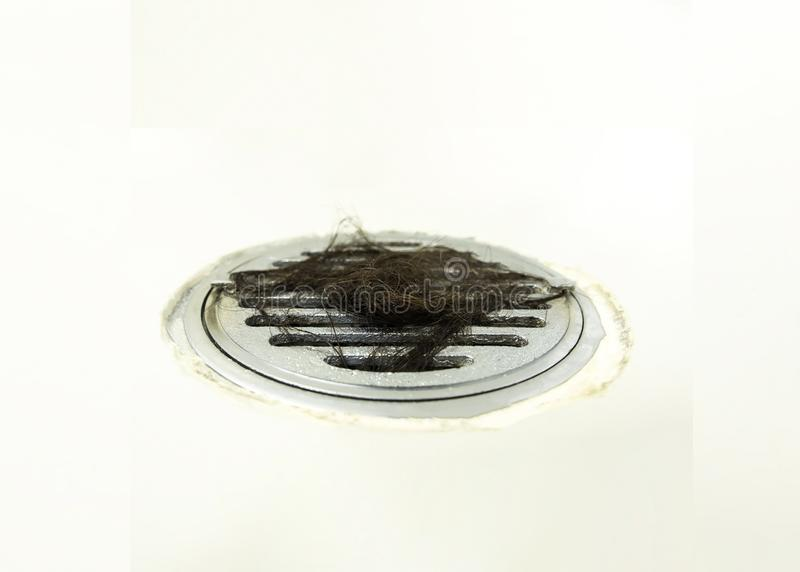 Hair loss clogged drain close up on white floor in bathroom, blurred photo stock images