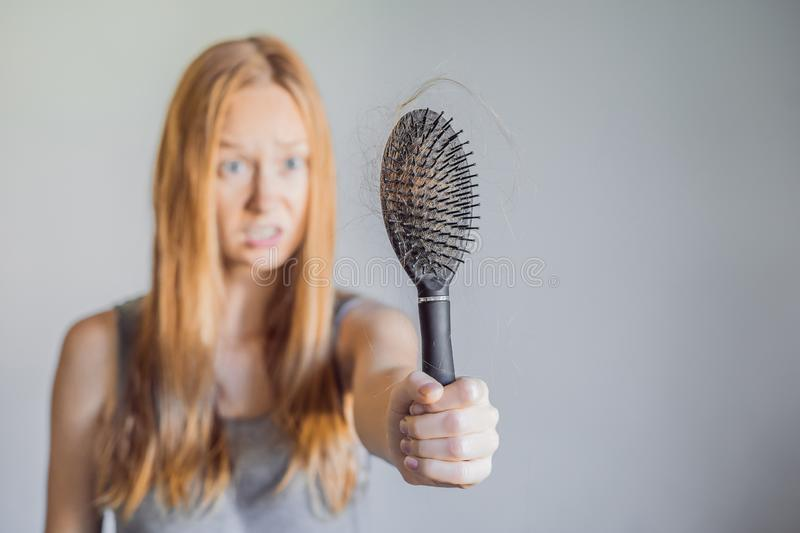 Hair loss in women concept. A lot of lost hair on the comb. Hair loss in woman concept. A lot of lost hair on the comb royalty free stock photos