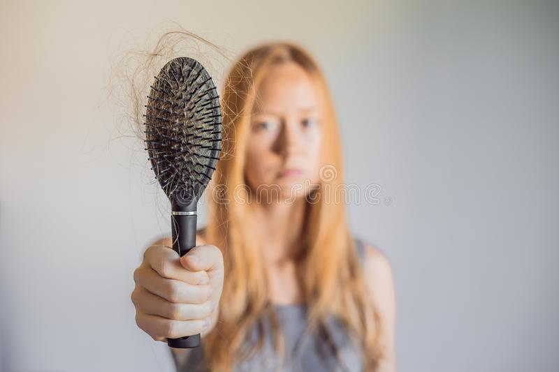 Hair loss in women concept. A lot of lost hair on the comb royalty free stock photos