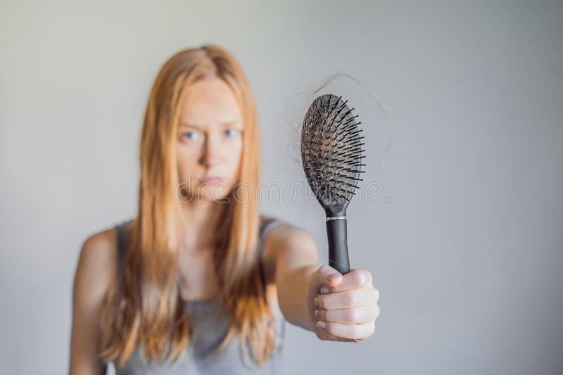 Hair loss in women concept. A lot of lost hair on the comb royalty free stock photo
