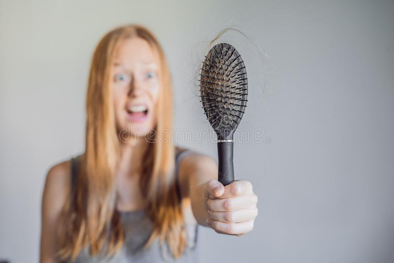 Hair loss in women concept. A lot of lost hair on the comb. Hair loss in woman concept. A lot of lost hair on the comb royalty free stock images