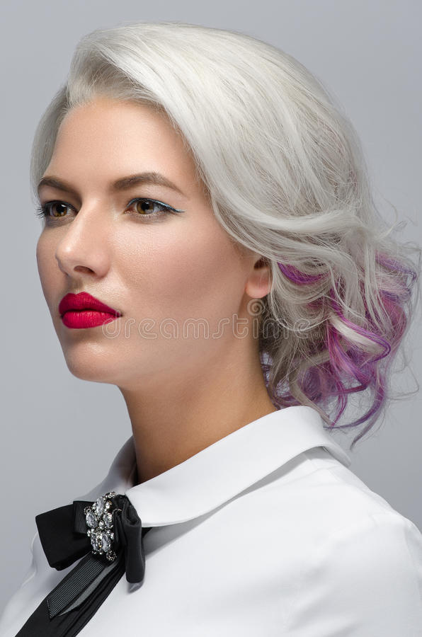 Hair and make-up theme: beautiful young blond woman with creative hair styling with red lips on gray background in studio. Hair and make-up theme: beautiful royalty free stock images