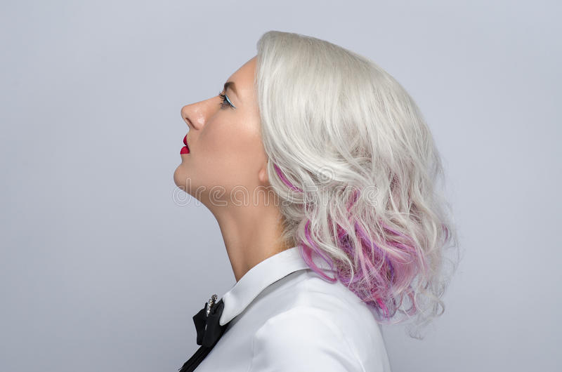 Hair and make-up theme: beautiful young blond woman with creative hair styling with red lips on gray background in studio. Hair and make-up theme: beautiful royalty free stock photos