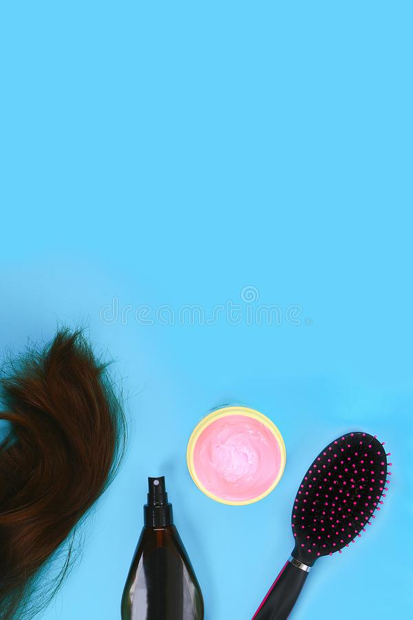 Hair, hair mask, comb, spray on pastel blue background. concept of hair care. Copy space, top view. Hair, hair mask, comb, spray on a pastel blue background. The royalty free stock photography