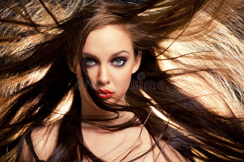 Hair in motion. Close up portrait of young brunette woman, with her hair in motion
