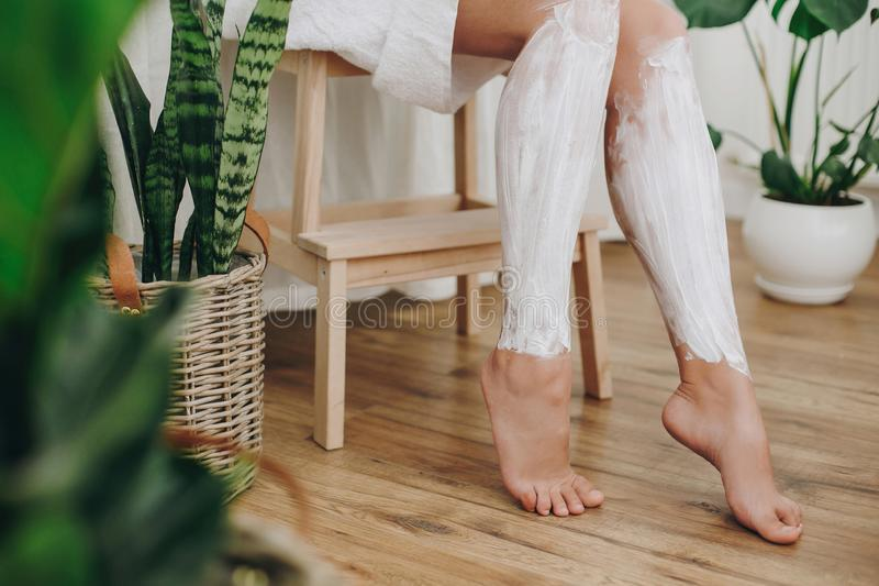 Hair Removal concept, depilation cream. Young woman in white towel applying shaving cream on her legs in home bathroom with green. Plants. Skin care and stock image